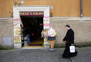 A member of the clergy passes a pizza and ice cream shop near Saint Peter's square
