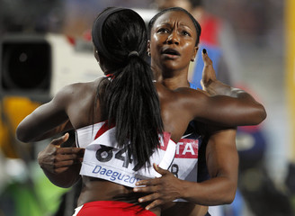 Carmelita Jeter of the U.S. embraces Kelly-Ann Baptiste of Trinidad and Tobago after winning the women's 100 metres final in Daegu