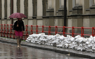 A woman walks past sand bags piled up on a street in central Prague