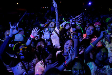 Participants dances after a nocturnal 5K color glow party run in Monterrey