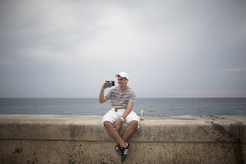 Artist Dariel Llerandis, 31, speaks to his wife who is in Miami using the internet at a Wi-Fi hotspot in Havana