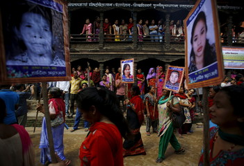 People holding portraits of their relatives who were killed in the April earthquake take part in a memorial rally in Bhaktapur