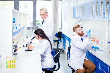 Teambuilding concept. Three workers of laboratory are ckecking the analysis. They look stylish, wearing labcoats. The lab is bright white and blue