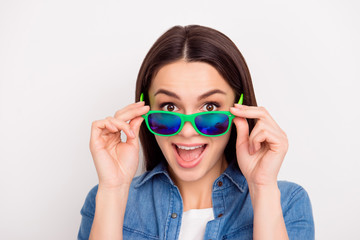 Closeup photo of beautiful funny girl in jeans shirt touching green sunglasses
