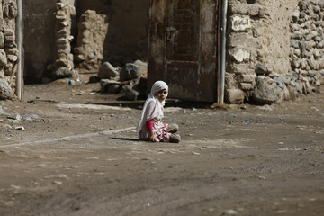 Girl sits on the ground as she plays outside her house in an outskirt of the Yemeni capital Sanaa