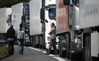 A group of migrants walk past a line of lorries waiting on the motorway which leads to the Channel Tunnel terminal in Calais