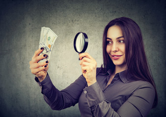 woman looking at one hundred dollar bills through magnifying glass