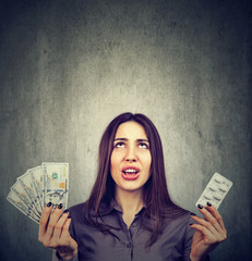 Healthcare costs. Upset woman with pills and dollar banknotes