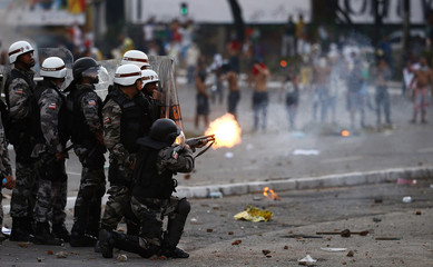 Law enforcement troops fire tear gas as they stop a demonstration outside the stadium before the Confederations Cup soccer match between Nigeria and Uruguay in Salvador
