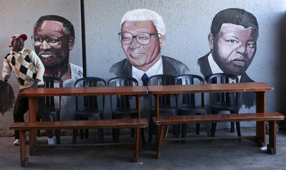 A man sits next to paintings of the late ANC president Oliver Tambo, South African anti-apartheid activist Walter Sisulu and African National Congress leader and former South African president Nelson Mandela at a shop house in Soweto
