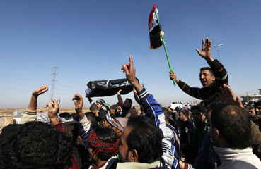 Residents carry a mock coffin during a protest to demand for better basic services in northern Baghdad