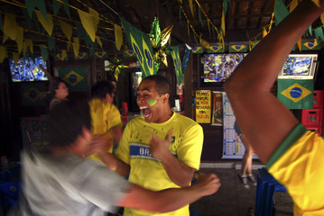 Brazilian supporters celebrate in a small outdoor bar in Brasilia June 28, 2014 after watching on television their team defeat Chile in their World Cup round of 16 soccer match