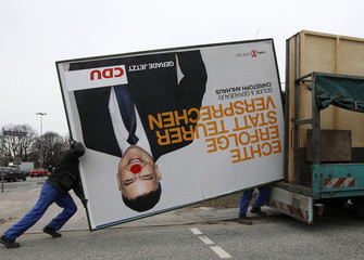 Workers load election campaign billboard showing Hamburg mayor Ahlhaus of CDU onto their truck following state elections in Hamburg
