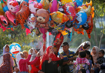 Muslims children buy balloons after attending Eid al-Fitr prayers to mark the end of the holy fasting month of Ramadan at Sunda Kelapa port in Jakarta,  Indonesia