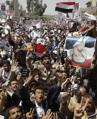 Anti-government protesters shout slogans while holding a picture of Yemeni President Ali Abdullah Saleh during a demonstration calling for his ouster, in Sanaa