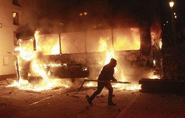 A pro-European integration protester runs past a burning police van during a rally near government administration buildings in Kiev