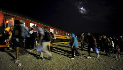 Migrants rush to board a northbound train, at Macedonia's south border near Gevgelija