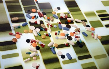 Pharmaceutical tablets and capsules are arranged on a background printed with a DNA pattern in this picture illustration taken in Ljubljana