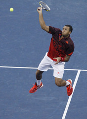 Jo-Wilfried Tsonga of France leaps into the air as he comes to the net against Mardy Fish of the U.S. during their match at the U.S. Open tennis tournament in New York