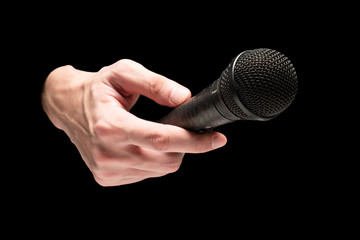 Male hand holding microphone on a black background.