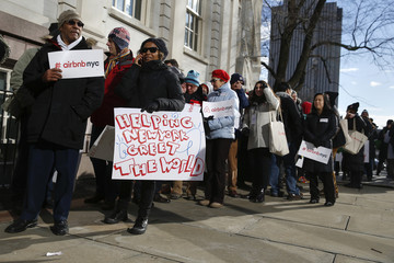 """Opponents of Airbnb rally before a hearing called """"Short Term Rentals: Stimulating the Economy or Destabilizing Neighborhoods?"""" at City Hall in New York"""