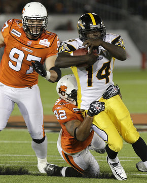 Hamilton Tiger Cats Cobb is tackled by BC Lions McKenzie as Lions Johnson gives chase during their CFL football game in Vancouver