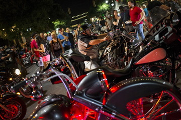 A man sits on his motorbike along Sixth Street after the Republic of Texas (ROT) Biker Rally bike parade in Austin, Texas