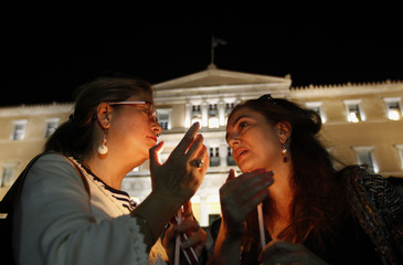 Protesters hold candles in front of the parliament during a rally by college and university professors against the new austerity measures, in Athens