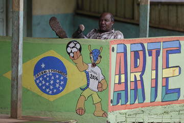 A man sits behind a wall painted with the 2014 World Cup mascot in Oiapoque