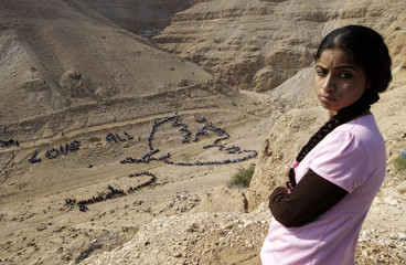 A Palestinian girl stands on the side of a mountain while other children stand to form Picasso's Dove of Peace as part of a project by artist Quigley and UNRWA, at the foot of the Mount of Temptation in Jericho