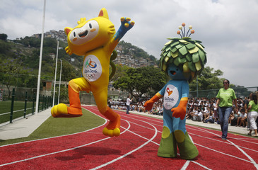 The unnamed mascots of the Rio 2016 Olympic and Paralympic Games are pictured with the Morro dos Prazeres slum in the background during its presentation in Rio de Janeiro