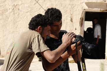 Free Syrian Army fighters inspect a camera in the suburb of Raqqa