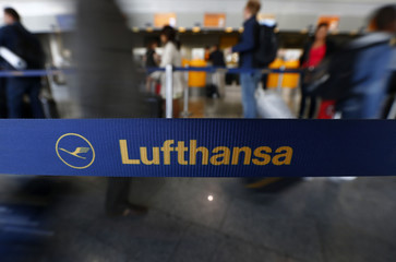 Passengers of German air carrier Lufthansa queue at a baggage drop-off at Fraport airport in Frankfurt