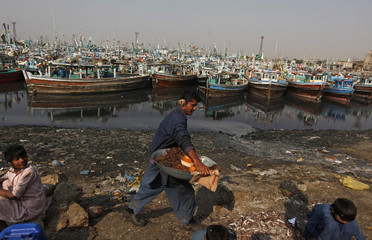 A man carries samosas to sell along Karachi's Fish Harbour
