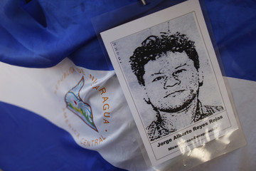 A photo of a missing migrant is seen on Nicaragua's flag during the arrival of the Caravan of Central American Mothers at Tultitlan