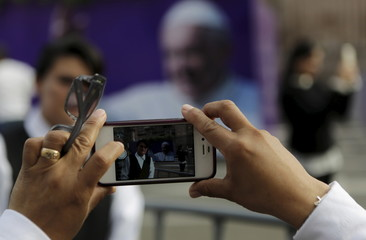 A woman takes pictures with her cell phone of an image of Pope Francis, outside the Cathedral, ahead of his visit to Morelia