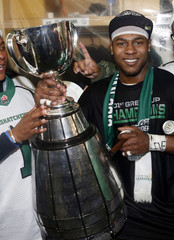 The Saskatchewan Roughriders Kory Sheets holds the Grey Cup in the dressing room after the Roughriders defeated the Hamilton Tiger-Cats in the CFL's 101st Grey Cup championship football game in Regina