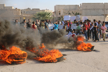People gather near burning tyres during a demonstration against forces loyal to Syria's president Bashar al-Assad and calling for aid to reach Aleppo near Castello road in Aleppo