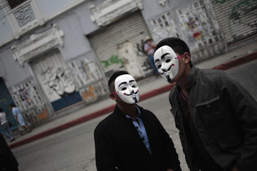 Protesters wearing masks stand at the entrance of Congress in Guatemala City