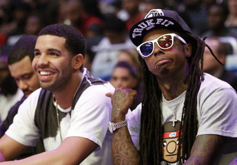 Rap artists Lil' Wayne  and Drake sit courtside during the NBA All-Star game in Orlando, Florida