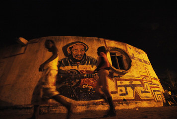 Children walk past a portrait of Bob Marley in Vridi's Village Rasta, Abidjan