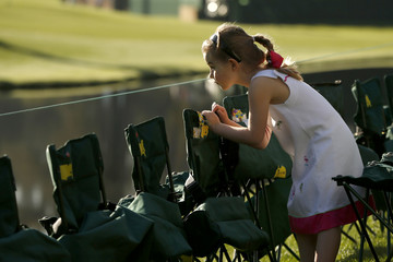 A young girl leans over here chair as she watches play during a practice round in preparation for the 2013 Masters golf tournament in Augusta