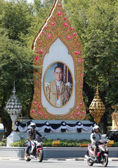 Thais ride on their motorcycles past a picture of Thailand's late King Bhumibol Adulyadej during the mourning period in Bangkok