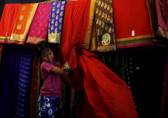 A girl works on a market stall selling saris for Diwali celebrations in Kuala Lumpur, Malaysia