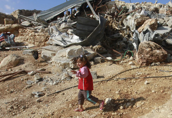 A Palestinian girl runs past her family's home after it was demolished by Israeli bulldozers in Khirbet Al-Taweel village near the West Bank City of Nablus