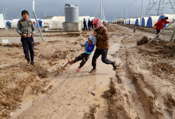 Displaced Iraqis who fled the Islamic State stronghold of Mosul, walk in the mud following heavy rain at Khazer camp