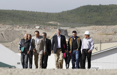 Canada's PM Harper walks to a news conference at Capstone Mining Corporation's Minto Mine