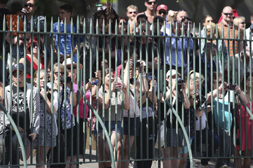 A crowd watches from behind a fence as Britain's Prince Harry salutes the troops at Garden Island during the International Fleet Review in Sydney