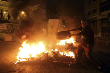 A relative of Lebanese soldiers burns tyres in a protest in Beirut
