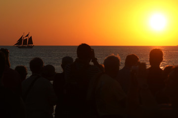 People take photos at sunset in Key West